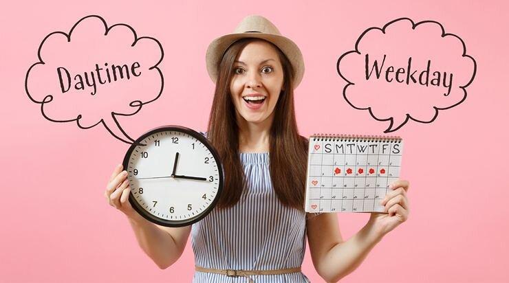 時計とカレンダーを持って喜んでいる女性の画像