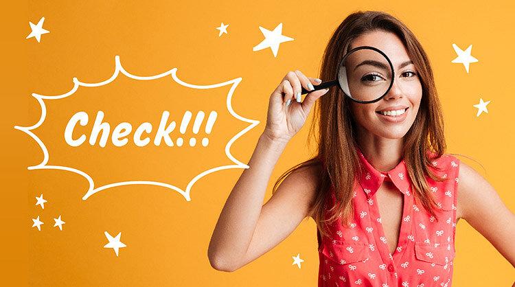 虫眼鏡で確認している女性の画像